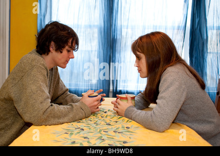 Teen couple talking over coffee or tea, at a yellow table. - Stock Photo