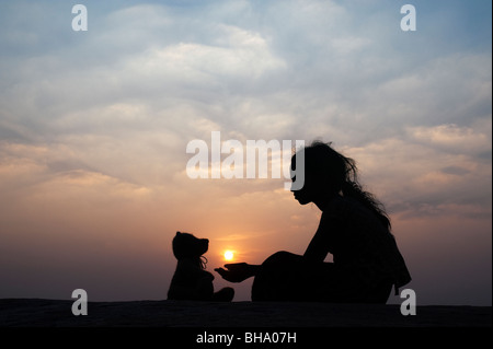 Indian girl holding the sun with her teddy bear at sunset. Silhouette. India - Stock Photo