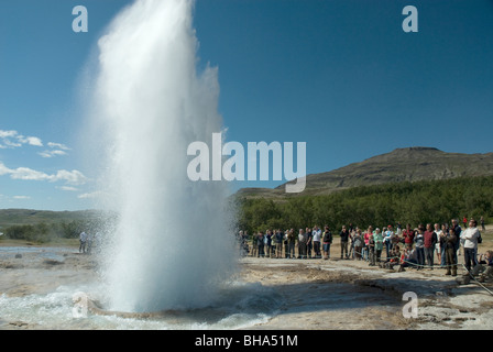 A group of people watching Strokkur Geysir erupt, Haukadalur, Iceland - Stock Photo