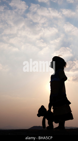 Little indian girl and her teddy bear at sunset. Silhouette. India - Stock Photo