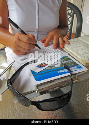 Woman writing postcards on holiday at Airlie Beach in Queensland - Stock Photo