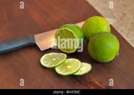 Cutting fresh limes on a chopping board - Stock Photo
