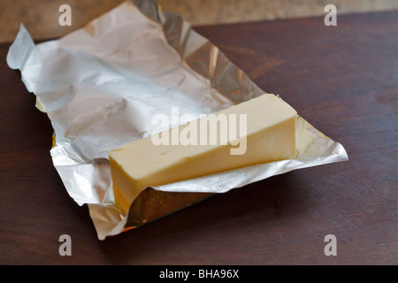 One quarter pound of butter in kitchen with foil wrapping - Stock Photo