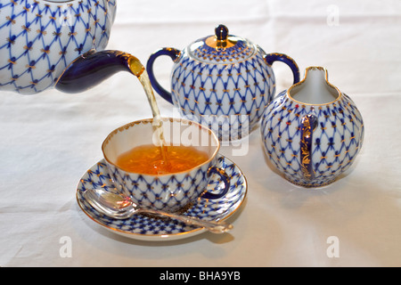 Tea being poured into a china cup - Stock Photo