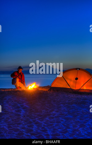 Man sitting at campfire with Cook Inlet and Mt. Redoubt in the background, Kenai Peninsula, Southcentral Alaska, - Stock Photo