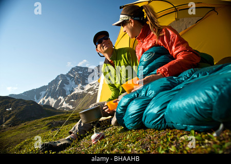 Hikers enjoy a morning meal at camp on the Williwaw Lakes Trail in Chugach State Park near Anchorage,Southcentral - Stock Photo