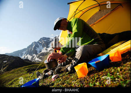 Hikers prepare a morning meal at camp on the Williwaw Lakes Trail in Chugach State Park near Anchorage,Southcentral - Stock Photo