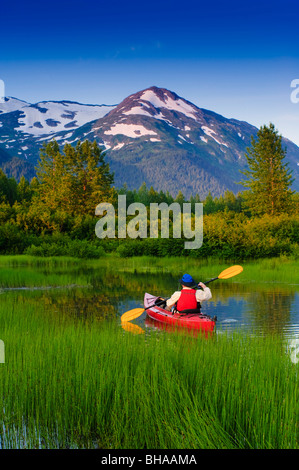 Man in a kayak paddling in a small lake in Portage Valley, Southcentral, Alaska, Summer - Stock Photo