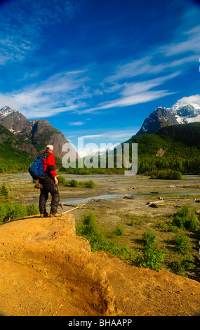 Hiker stands on a rock outcrop overlooking Eagle River, Chugach State Park, Southcentral Alaska, Summer - Stock Photo