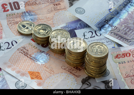 Five piles of one pound coins in increasing height on a background of fifty, twenty and ten pound notes. - Stock Photo