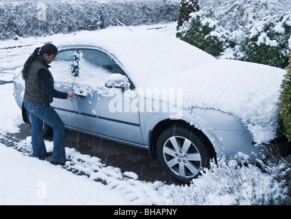 A young woman trying to open snow covered parked car door in severe wintry condition of snowfall on trees, roads, - Stock Photo