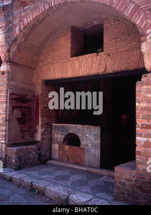 Ostia Antica the ancient port of Rome - the ancient snack bar booth on the Decumanus Maximus main street - Stock Photo