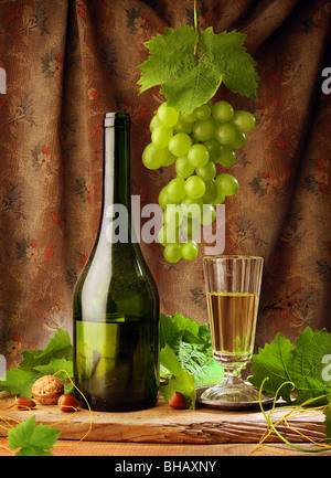 Wine still life in vintage style, with white wine bottle, glass, grape and fresh grapevine leaves - Stock Photo