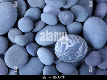 Close up of smooth granite pebbles on Hurlestone beach, Somerset, England filling frame. - Stock Photo