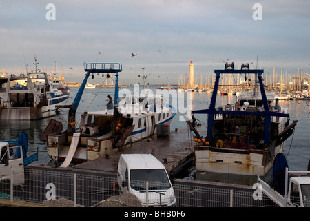 In Sète, France's largest Mediterranean fishing port, trawlers are quietly moored as the evening sun brightens the lighthouse