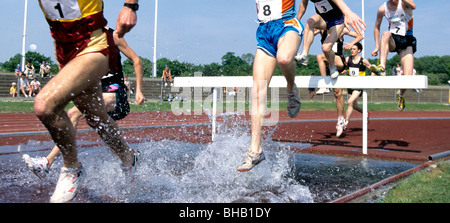 Group of male runners jumping over hurdles during a steeplechase - Stock Photo