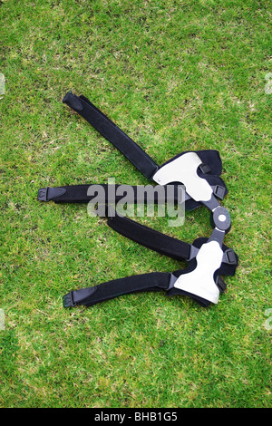 Footballers knee brace lies in grass after a game - Stock Photo