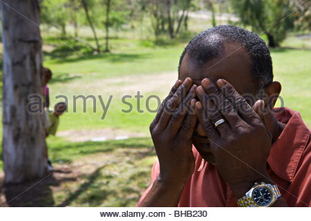 Children (6-10) playing hide and seek with grandfather in park, senior man covering eyes - Stock Photo