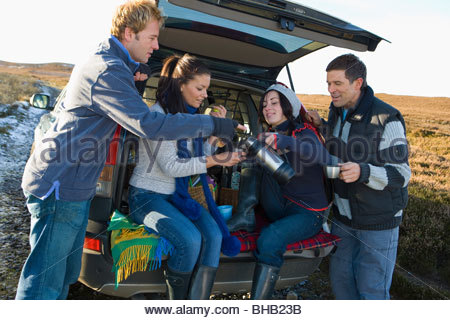 Friends enjoying coffee in back of car on remote road - Stock Photo