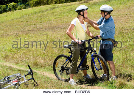 Couple with bicycles in countryside, man adjusting woman's helmet - Stock Photo