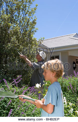 Father and son (8-10) gardening, boy with hose, side view - Stock Photo