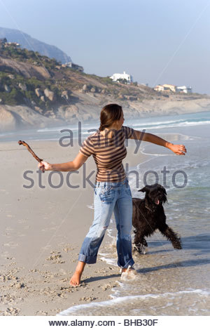Woman preparing to throw stick for dog on beach - Stock Photo