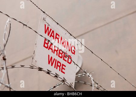Sign on barbed wire fence 'Warning Barbed Wire' - Stock Photo