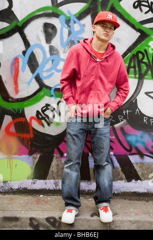 Hispanic Teenager against graffiti wall - Stock Photo