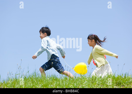 Japan, Tokyo Prefecture, Children holding balloons running through meadow, side view - Stock Photo