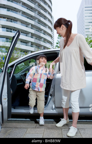 Japan, Tokyo Prefecture, Mother and daughter getting off car - Stock Photo
