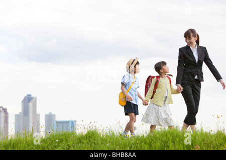 Japan, Tokyo Prefecture, Mother and children  walking through meadow, skyscrapers in background - Stock Photo