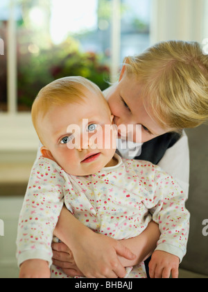 A little girl hugging her baby sister - Stock Photo