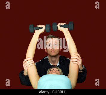 A fitness trainer helping a client - Stock Photo