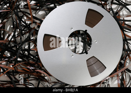 Red tape spilling out from a large reel of magnetic recording tape - Stock Photo