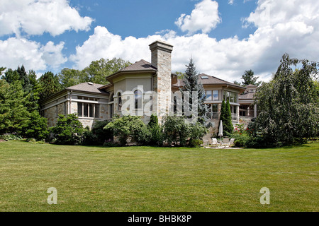 Large suburban stone home with terrace and patio - Stock Photo