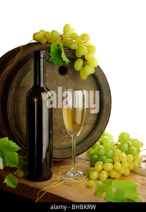 Still life with white wine bottle, glass, old wine barrel, grapes and fresh grapevine leaves, isolated on white - Stock Photo