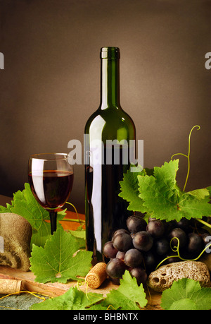 Still life with red wine bottle, glass, grapes and fresh grapevine leaves on dark background - Stock Photo