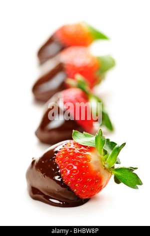 Row of strawberries dipped in delicious chocolate isolated on white - Stock Photo