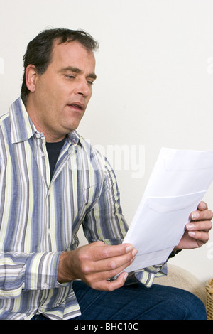 Man reading letter or official document looking astonished, holding  an unclear and confusing paper in his hand - Stock Photo