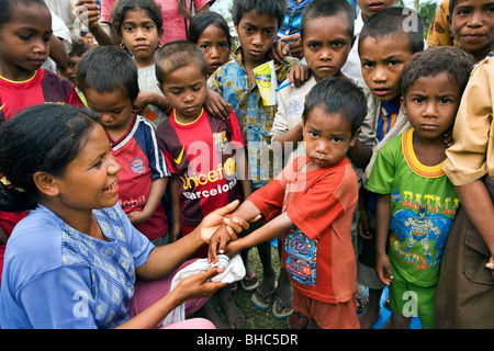 Brigitte Madeira of Oxfam-Covalima teaches children hygiene and cleanliness at remote impoverished Welua village - Stock Photo