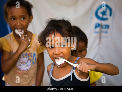 Cleaning teeth PLAN provide water sanitation toothbrushes toothpaste for children at IDP displaced persons camp - Stock Photo