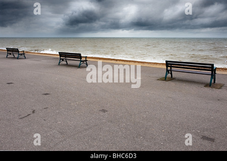 Three empty benches on the seafront at Deal in Kent. - Stock Photo