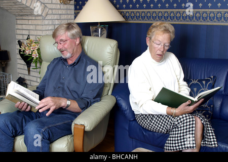 Middle aged couple back to back nothing to say reading a book - Stock Photo