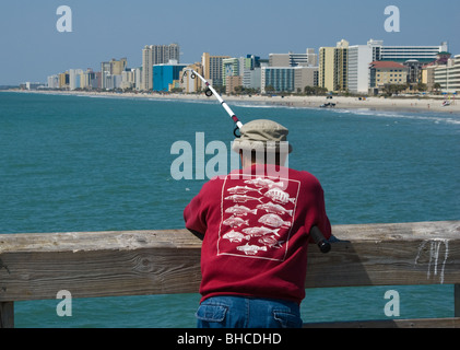 Man fishing from a pier in Myrtle Beach, South Carolina, USA - Stock Photo