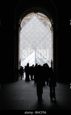 View of Louvre Museum Glass Pyramid Through Entrance with Tourists - Stock Photo