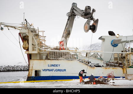 Fishermen on fishing boat Lundey. Vopnafjordur harbour, East Iceland. - Stock Photo