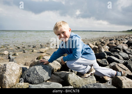 Boy walking over stones - Stock Photo