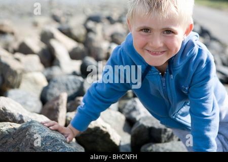 Boy sitting on stones - Stock Photo