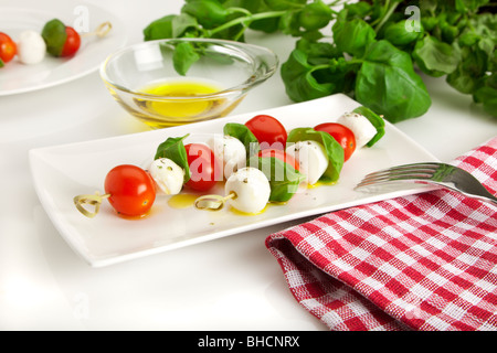 caprese salad sticks - spitted cherry tomatoes, mozzarella balls and basil leaves on a rectangular plate, refined with olive oil