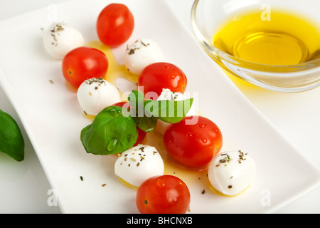 mozzarella cheese balls spitted with tomatoes and basil leaves with olive oil nad herbs on a plate